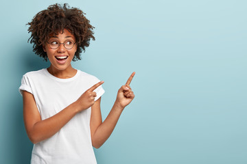 Beautiful black woman looks to side, shows free advertising space, smiles broadly, dressed in white casual t shirt, isolated over blue background, wears spectacles for good vision. Its for your ad