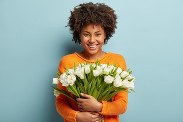 Indoor shot of beautiful smiling young woman with Afro haircut holds big bouquet of spring white flowers, rejoices coming Womens Day soon, dressed in orange jumper, isolated over blue background.