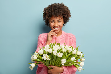 Photo of pleasant looking dark skinned woman with cheerful facial expression, satisfied with something, carries white first spring flowers, wears oversized jumper, isolated over blue background.