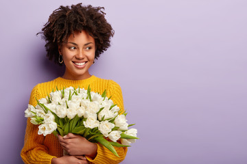 Horizontal shot of good looking black woman with spring flowers bouquet, keeps gaze aside, has curly hairstyle, wears yellow jumper, models over purple background with blank space for information