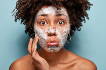 Cropped image of shocked young woman with Afro hairstyle, washes face with cleansing lotion, has bugged eyes, poses nude against blue background, enjoys softness of skin. Beauty and cosmetology
