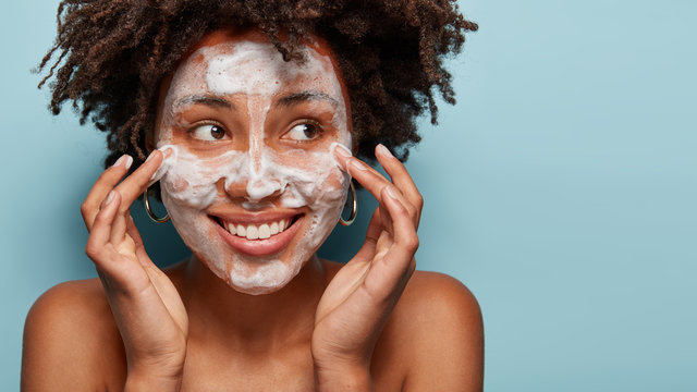 Satisfied beautiful black woman makes massage of face, has white foam, problem of wide pores, cares of skin, keeps gaze aside, smiles positively, models over blue studio wall with free space