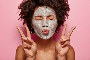 Photo of attractive woman keeps lips folded, has clay mask on face, foolishes indoor, makes peace gesture, poses naked, closes eyes with pleasure, isolated over pink background. Beauty concept
