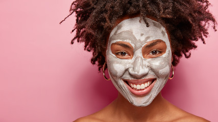 Positive ethnic woman with toothy smile, crisp hair, white clay mask applied on face, looks at camera happily, has beauty treatments in spa salon, models against pink background with free space aside