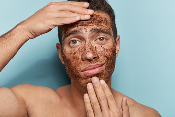 Close up photo of displeased young masculinity man has coffee scrub on face, touches chin and forehead, poses topless, models against blue background, visits cosmetologist. Wellness concept.