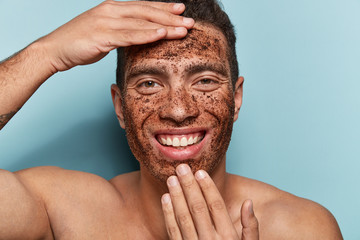 Photo of cheerful Caucasian man with coffee scrub mask on face, touches forehead and chin, smiles broadly, shows white perfect teeth, has muscular body, models in studio agaisnt blue background