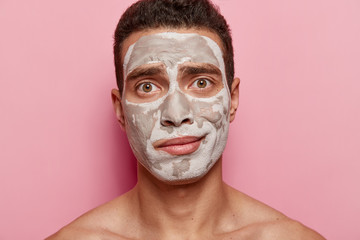 Close up portrait of young male model has white clay mask on face, poses topless against pink background, looks directly at camera with dark brown eyes. Men, beauty and facial treatments concept