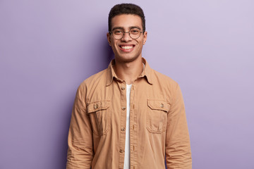 Handsome smiling guy wears spectacles and beige shirt, looks at camera with satisfaction, enjoys getting new job position, isolated over purple background. Youth and positive emotions concept