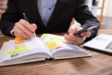 Fototapete - Businessman Holding Cellphone Writing Schedule In Diary With Pen