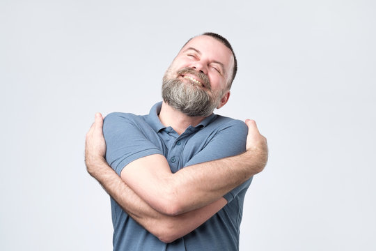 Funny selfish mature european guy in blue shirt cuddling himself