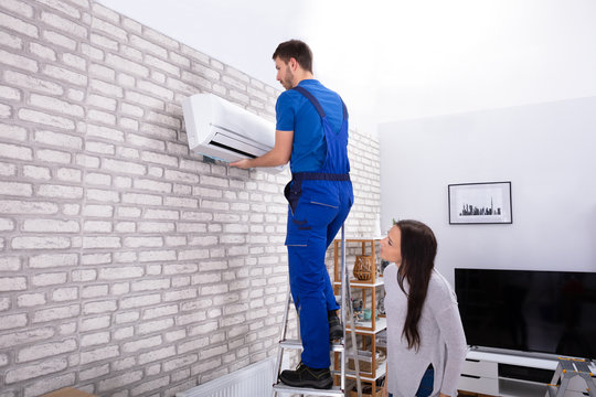 Male Technician Fixing Air Conditioner On Wall