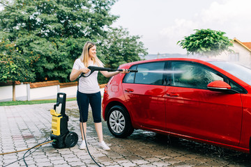 Young woman washing her carr using high pressure water. Selective focus.