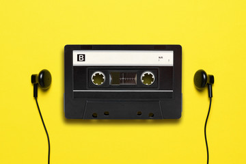 Headphones and old audio cassette on yellow background