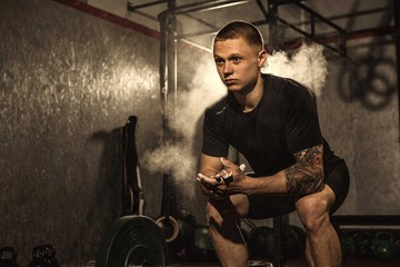 Horizontla low angle portrait of a young tattooed male athlete clapping his hands with magnesium. Fierce cross fit man preparing for workout at the gym. Concentration, focusing concept