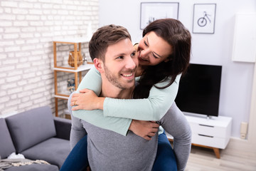 Happy Man Giving Piggyback To His Wife At Home