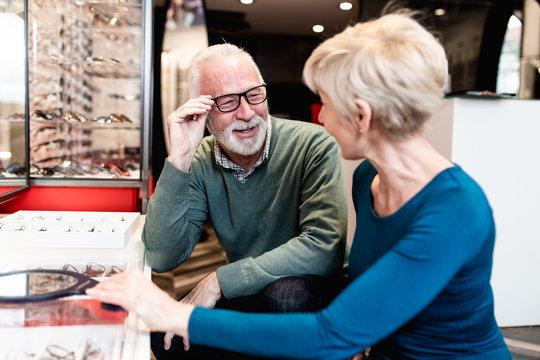 Happy senior couple choosing together eyeglasses frame in optical store.