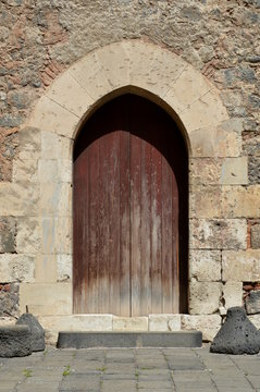 Old wooden door in stone wall, Sicily, Italy