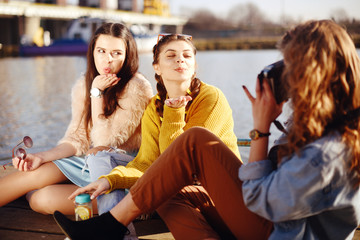 The blonde girl takes pictures of her brunette girlfriends on the old camera. They send her kisses, smile, laugh. Girl with drinks and sunglasses have fun. Girls on the dock/pier on the back of yachts