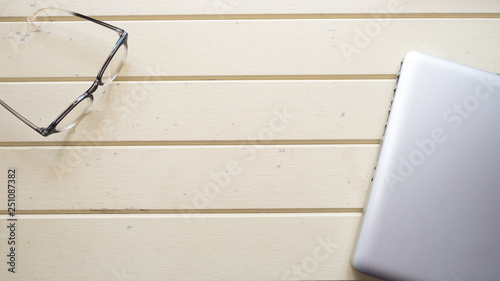 Wall mural glasses and  laptop copy space on wood background