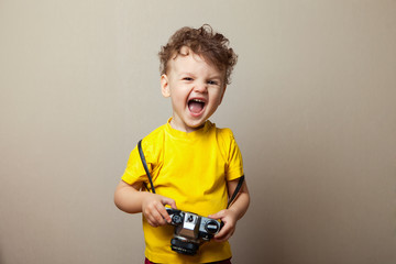 Little kid boy 2years old wearing yellow clothes hold camera isolated on grey wall background, children studio portrait. People sincere emotions, childhood lifestyle concept. Mock up copy space