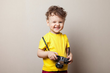 Little kid boy 2 years old wearing yellow clothes hold camera isolated on grey wall background, children studio portrait. People sincere emotions, childhood lifestyle concept.