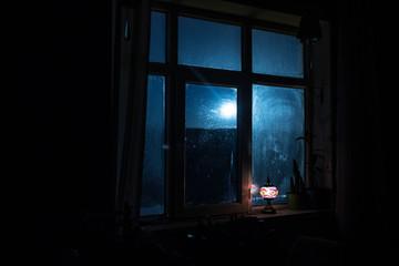 Night scene of stars seen through the window from dark room. Night sky inside dark room viewing from window with old vintage lantern. Long exposure shot