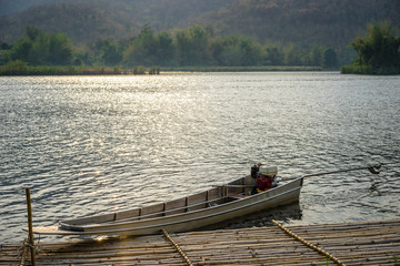 boats docked on a mountain lake with sunlight.Natural dam lake in forest.