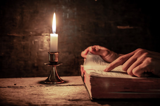 Close up hands of man readidng bible with light of candle on wooden table. christian concept.
