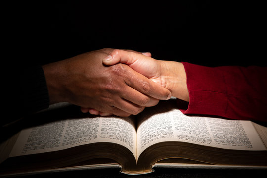 Hand Shake Over the Bible Signaling Religious Understanding