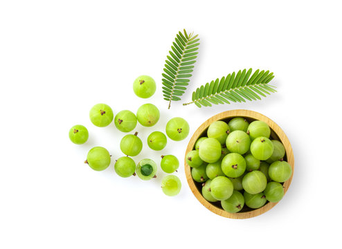 Indian gooseberry in wood bowl on white background. top view
