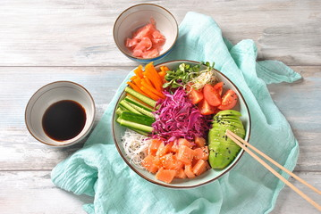 Fresh seafood recipe. Organic food. Fresh salmon poke bowl with crystal noodles, fresh red cabbage, avocado, cherry tomatoes. Food concept poke bowl