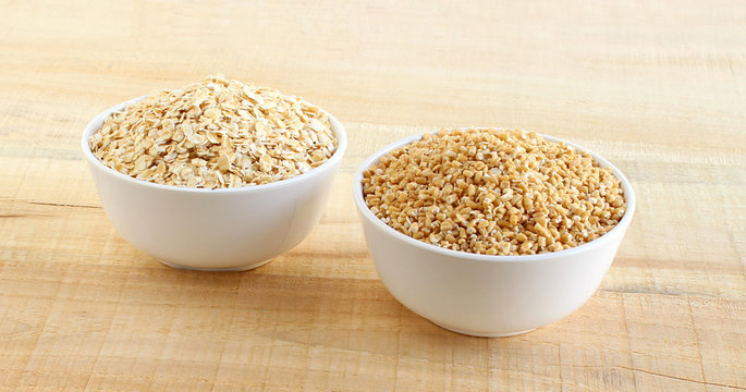 Healthy food oats and steel-cut oats each in a bowl on a wooden background.