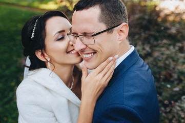 In love and smiling newlyweds kiss in the fall against the backdrop of bushes. Closeup portrait of stylish groom in glasses and cute bride in white dress. Wedding photography.