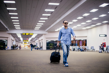 Asian man traveler with suitcases walking and transportation at an airport