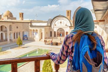 Young female tourist enjoying view of Iranian courtyard, Kashan