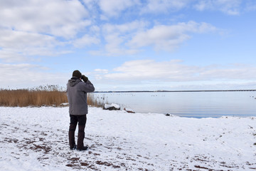 Birder by a coast in winter season