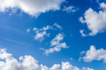 Fluffy white clouds against a bright, colorful blue sky