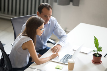 Female and male looking at laptop screen discussing working moments