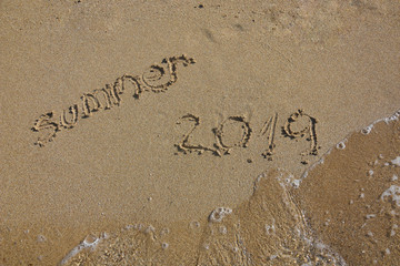 Summer vacation concept. Summer 2019 written on wet sand at the beach