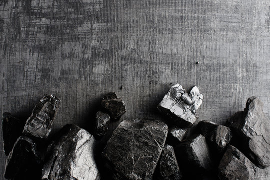 Natural coal on a black background isolated closeup. Extraction of natural mineral resources.