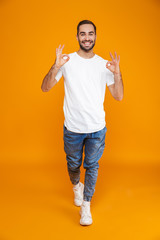 Full length image of beautiful guy 30s in t-shirt and jeans showing ok sign while standing, isolated over yellow background