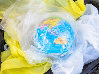 A terrestrial globe or planet Earth between garbage and plastic bags. Concept of ecology