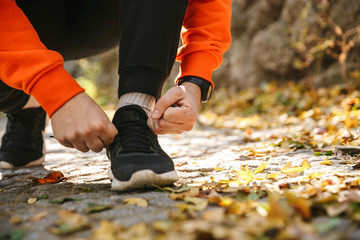 Sports fitness man runner outdoors in park listening music tie laces.