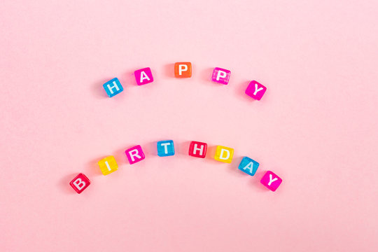 Happy birthday inscription made of colorful cube beads with letters. Festive pink background concept with copy space
