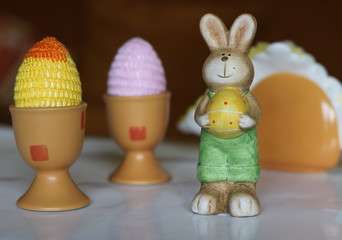 Figurka wielkanocnego zajączka z żółtym jajkiem w łapkach, obok dwie kolorowe pisanki z...