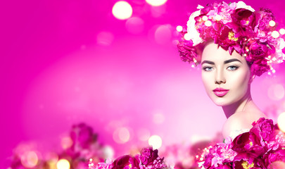 Flowers hairstyle. Beauty model girl with pink peony flowers wreath over purple background