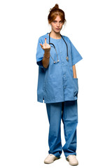 A full-length shot of a Young redhead nurse making horn gesture over isolated white background