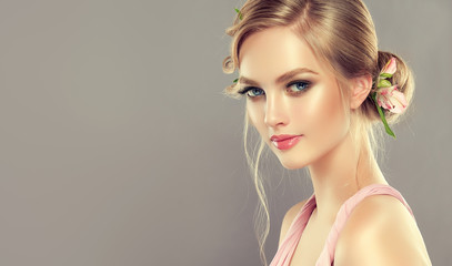 Beautiful model girl  with elegant hairstyle and rose flowers in a plait . Woman with fashion  spring hair. Wall mural