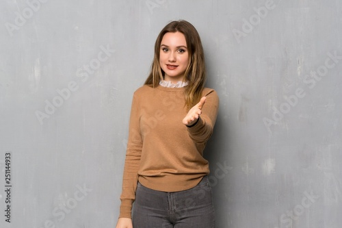 Teenager girl over textured wall shaking hands for closing a good