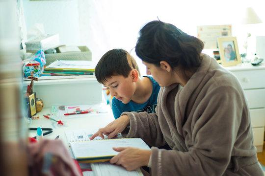 Madre ayudando a su hijo a estudiar y hacer los deberes o tareas escolares en casa
